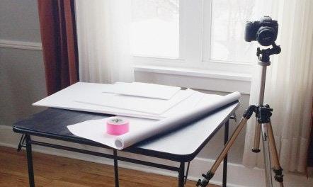 Configuración de estudio fotográfico DIY portátil: cámara, trípode, mesa plegable, papel sin costura